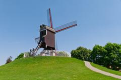 Wind mill and green lawn at Brugge - stock photo