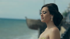 Tender young girl in gorgeous lemony strapless dress stay near the sea Stock Footage