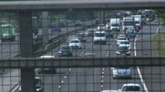 Looking through cage mesh at busy traffic on free way Stock Footage