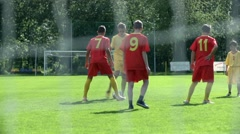 Boys in red and yellow dress playing soccer and hitting goal Stock Footage