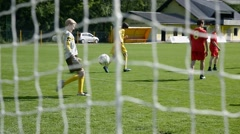 Soccer action on green field kicking and scoring goal - stock footage