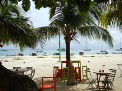 Beach bar, with palm, boats and sea - stock photo