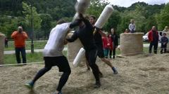 People running through pugil sticks obstacle course Stock Footage