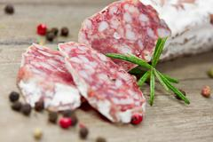 Sliced salami on wooden board Stock Photos