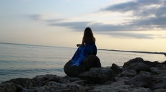 Lovely girl in a blue dress sitting on the rocks and looking into the distance Stock Footage