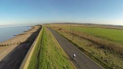 Stock Video Footage of aerial of cyclist along sea front