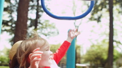 Mother Holds Her Little Boy Up To Reach The Monkey Bars Like A Big Kid Stock Footage