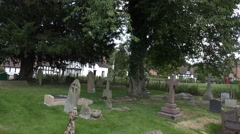 English village through trees in church yard Stock Footage