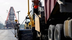 Asphalt compactors working on the construction of the bridge Stock Footage