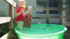 Two fully dressed kids in a kiddie pool playing toys Stock Footage