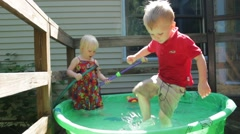 Boy stomps his foot in a kiddie pool Stock Footage