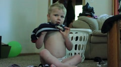 Three year old struggles to get his shirt on - stock footage