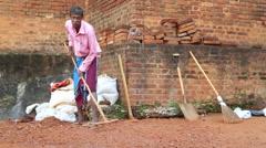 Local man raking stones in Sigiriya, Sri Lanka. Stock Footage