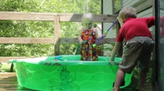 2 year old girl fills kiddie pool Stock Footage