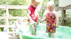 Boy and girl share a hose in the pool Stock Footage