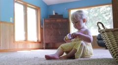 Beautiful 2 year old plays dollies and smiles Stock Footage