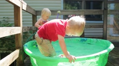 Fully clothed boy swoops a toy through a kiddie pool Stock Footage
