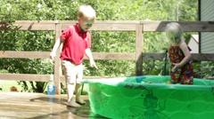 Boy runs around edge of kiddie pool as girl fills it with hose Stock Footage