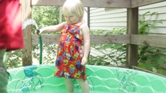 Girl chases boy with hose water Stock Footage