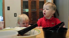 Toddlers howling at dinner table Stock Footage