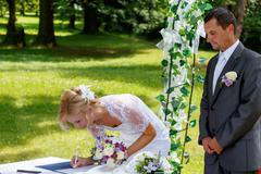 Beautiful blonde smiling bride signed contract Stock Photos