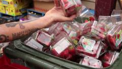 Tattooed man finds strawberry punnets in bin Stock Footage