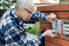 Handyman fixing intercom Stock Photos