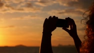 Stock Video Footage of Woman Taking Picture with Smartphone at Sunset in Sea Voyage. Slow Motion.