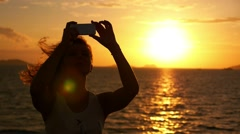 Woman Taking Pictures with Smartphone at Sunset. Selfie against Seascape. Slow Stock Footage