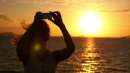 Stock Video Footage of Woman Taking Pictures with Smartphone at Sunset. Selfie against Seascape. Slow