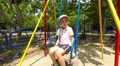 boy ride on a swing in the playground, slow motion 2 Footage