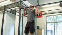 Trainer Executing Strict Pull Ups Body Weight Movement at a CrossFit Box Stock Footage