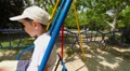 boy ride on a swing in the playground, slow motion Footage