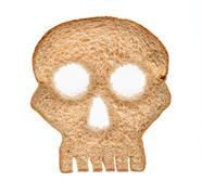 slice of wholewheat bread in shape of skull - stock photo