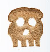 Slice of wholewheat bread in shape of skull Stock Photos