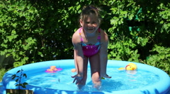 Cheerful girl in inflatable pool in summer garden Stock Footage