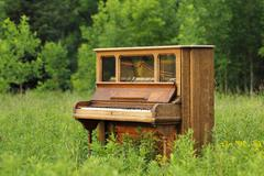 Old upright piano abandoned in a green field Stock Photos