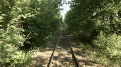 Railway travel through trees in summer 4K - stock footage