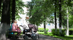 Two young mothers with buggies in the park Stock Footage