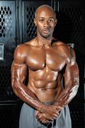 Portrait of a lean toned and ripped muscle fitness man under dramatic low key Stock Photos