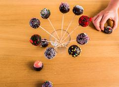 Cake-pops in stick in a glass with a helping hand Stock Photos
