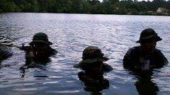 Pan Shot of Men in Camouflage Neck-Deep in Water - stock footage