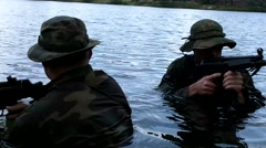 Men in Camouflage Exit Swamp  Stock Footage