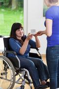 Female caregiver giving cup of tea to woman on wheelchair Stock Photos