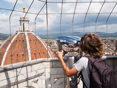 tourism concept: boy looking through a sightseeing binoculars the dome of flo - stock photo