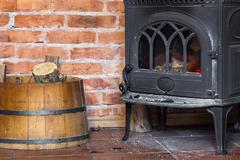 Fireplace with fire flame and firewood in barrel interior. heating. Stock Photos