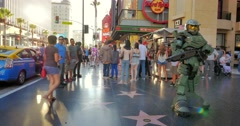 People walking by future soldier warrior on Hollywood Stars Walk of Fame in LA - stock footage