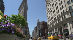 Flatiron Building behind the colourful flowers in Manhattan Stock Footage