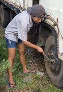 Female mechanic tighten wheel truck - stock photo