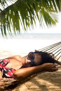 woman is resting in the hammock under the palms on the tropical beach - stock photo